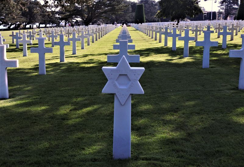 rows of marble headstones in american cemetery normandy