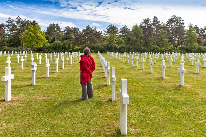 man standing in the middle of the american cemetery normandy