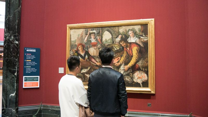 mens wathcing a painting in the national gallery london